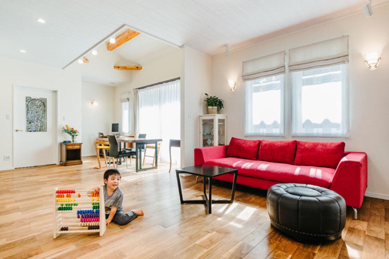 ナカゴミ建設【収納力、間取り、趣味】白を基調とした開放感あふれるLDK。赤いソファが差し色に。肌触りのいい床は無垢のウォールナットで、経年変化も楽しみ