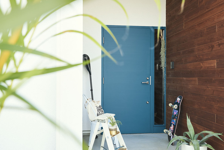 白い外壁にブルーの玄関。