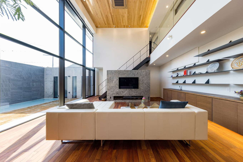 i.u.建築企画【高級住宅、建築家、鉄骨鉄筋コンクリート構造】LDKの南面には、高層建築でよく採用されるカーテンウォールを天井いっぱいまで取り付け、圧倒的な開放感を演出。一方、壁面にはオリジナルデザインのスチール製の造作棚を設け、美術品などをギャラリーのように美しく整然とディスプレイできるようにした