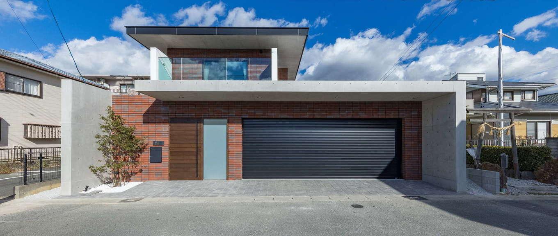 i.u.建築企画【高級住宅、建築家、鉄骨鉄筋コンクリート構造】RC壁式工法による2階建。コンクリートの打放しとレンガ調タイルを組み合わせた、クラシカルで重厚感のある外観がインパクトを放つ。夫妻の要望で、軒を深くしたフォルムが特徴的