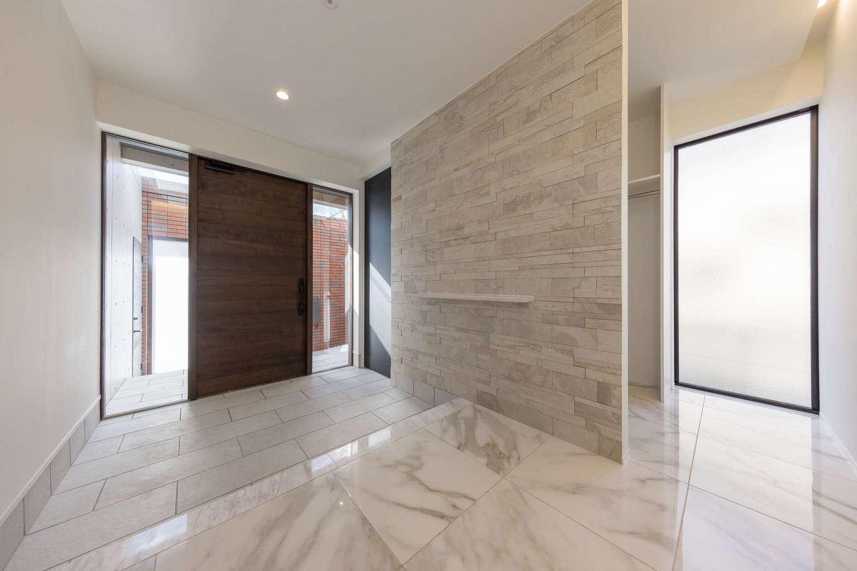 i.u.建築企画【高級住宅、建築家、鉄骨鉄筋コンクリート構造】玄関の土間や壁はタイル貼り、玄関ホールの床には大理石を用い、「住まいの顔」としてワンクラス上の洗練された空間を演出。大容量のシューズクロークと家族用の玄関も設けてある