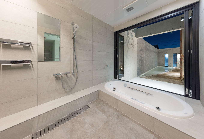 i.u.建築企画【高級住宅、建築家、鉄骨鉄筋コンクリート構造】バスルームはパウダールームと同様に壁・床ともに総タイル貼りで仕上げ、ホテルライクに演出。バスルームの窓をフルオープンにすると、中庭の水盤を眺めることができ、リゾートライクなバスタイムをゆったり楽しめる