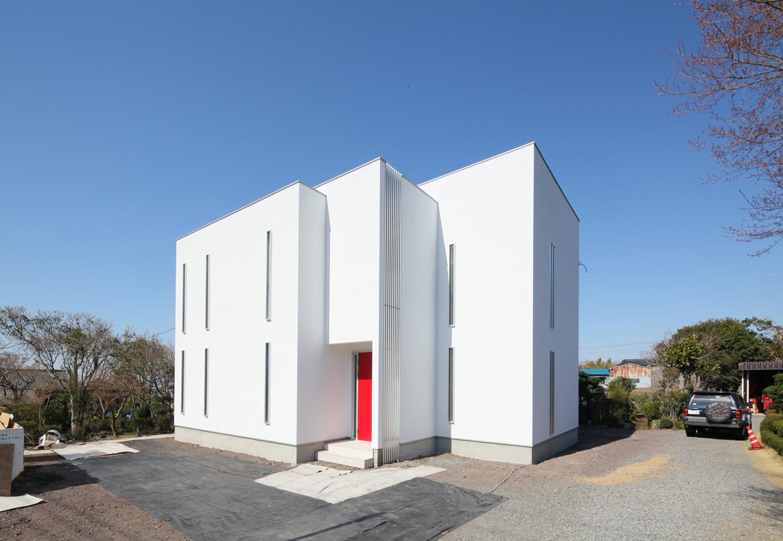 圧倒的な存在感を放ちたたずむ真っ白なモダンハウス。外観は高さの違う3つの箱が折り重なり、格子やスリットサッシで縦のラインが強調されたデザイン