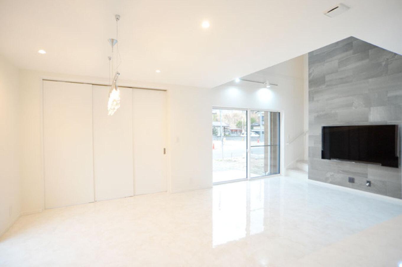 Nhouse【デザイン住宅、子育て、省エネ】リビングダイニングは大理石調のフロアタイル、TV台壁は吹き抜けを利用してタイルを張り、高級感もプラス
