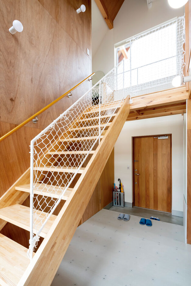 ナカゴミ建設【1000万円台】土間仕上げの玄関。スケルトン階段と吹抜けが気持ちいい