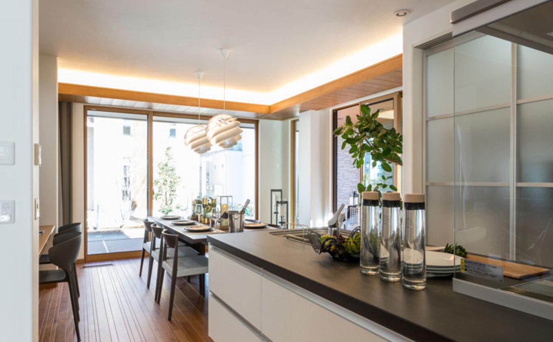 トヨタホーム【富士市今井348-4・モデルハウス】視界いっぱいに広がりを感じる二面開口で、ダイニングを囲うインナーパティオと一体化。キッチン背面には半透明の扉をつけ、すっきりと納めている