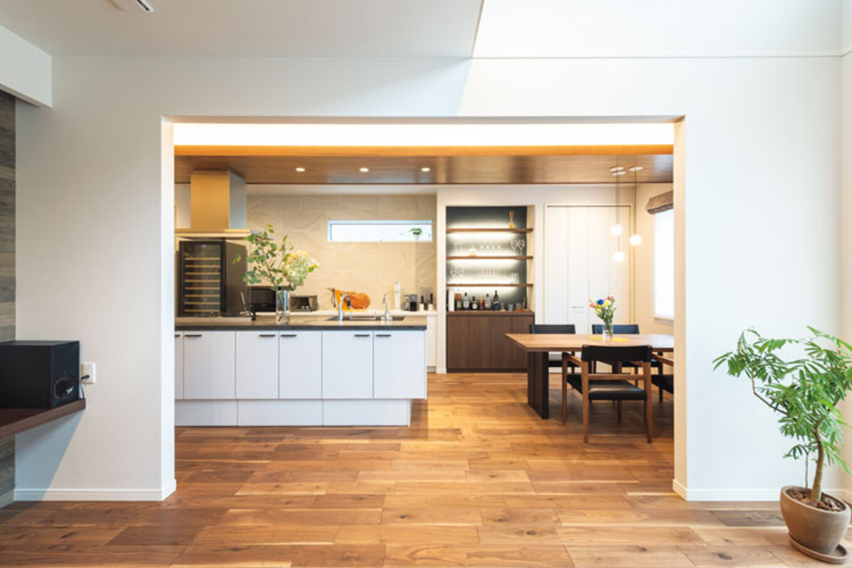 ウィザースホーム【1000万円台、デザイン住宅、子育て】リビングからつながるダイニング・キッチンは、下がり天井や特注の飾り棚の照明が映え、まるでホームバーの雰囲気。アイランドキッチンの背面は大判のアクセントタイルをあしらい、念願のワインセラーを設置
