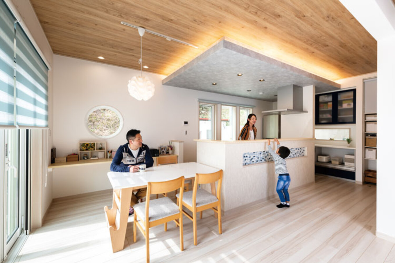 ウィザースホーム【1000万円台、デザイン住宅、子育て】白と青の色調がさわやかなダイニング・キッチン。キッチン上部の下がり天井と間接照明が引き立つ