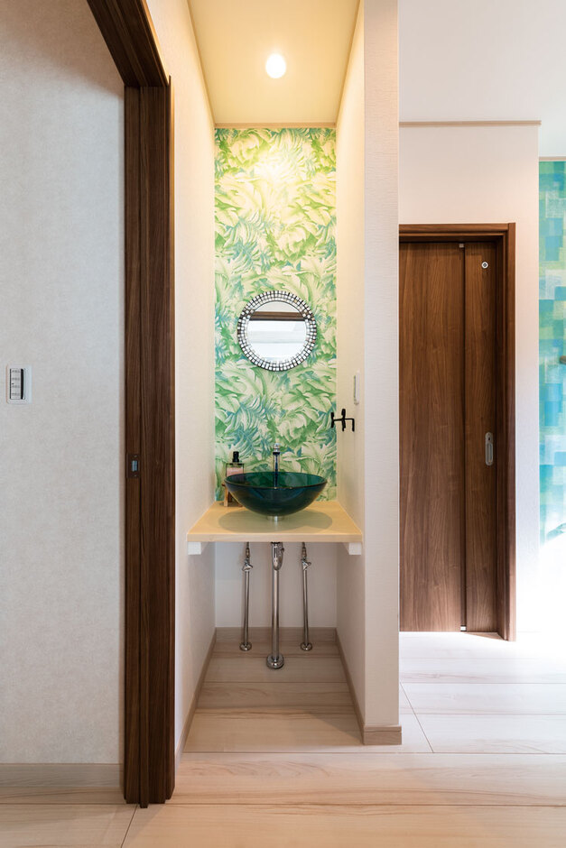 ウィザースホーム【1000万円台、デザイン住宅、子育て】玄関ホールの一角に設けたオープンな手洗いコーナー。グリーンのガラスボウルや植物柄のクロスが印象的。右奥のトイレは引き戸で車椅子のまま入れる広さとし、近くにはお母様用の部屋を用意するなど、将来の同居に向け細やかな配慮がされている