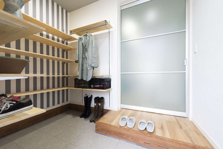 F.Bird HOUSE(袴田工務店)【収納力、趣味、間取り】玄関内の土間収納。靴はもちろん、上着やベビーカー、ゴルフバッグなども置ける。リビングに続く扉は光を通すミスト調の素材で、空間がより広く明るく感じられる