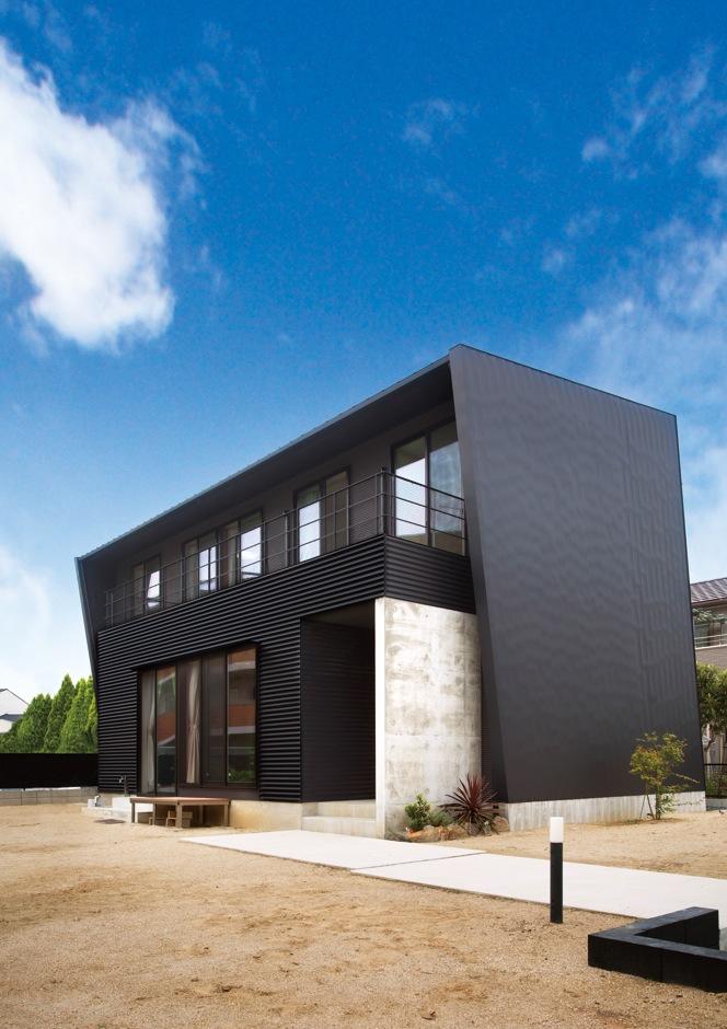 アトリエプラス【デザイン住宅、趣味、自然素材】大波と小波のガルバリウム鋼板をメインに、目隠しのためのRC壁がアクセントになっている。道路側の壁は窓をつくらず、物干し場の位置にも配慮