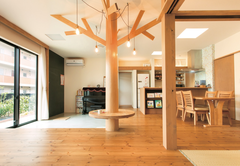 アトリエプラス【デザイン住宅、趣味、自然素材】土間とLDKが一体となったのびやかな空間。大黒柱をシンボルツリーに見立て枝をプラス。ツリーのテーブルと土間の黒板が子どもたちのお気に入り