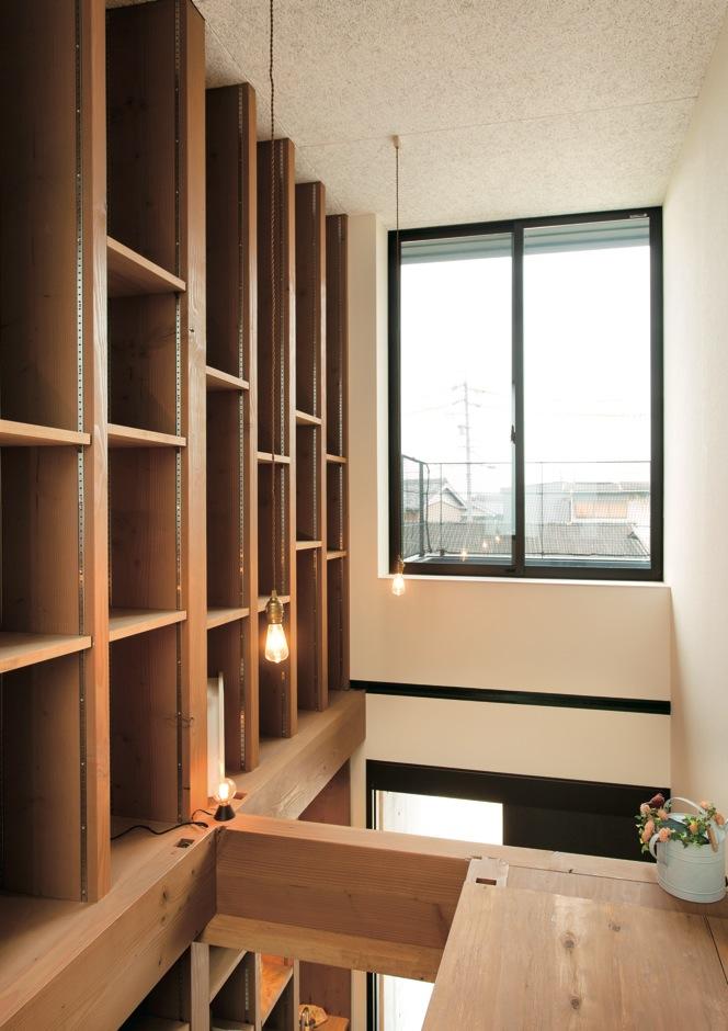 アトリエプラス【デザイン住宅、趣味、自然素材】土間収納の上部は本棚として活用。高窓から光と風が通る。吹き抜けはいずれ床を張ってご主人の書斎に