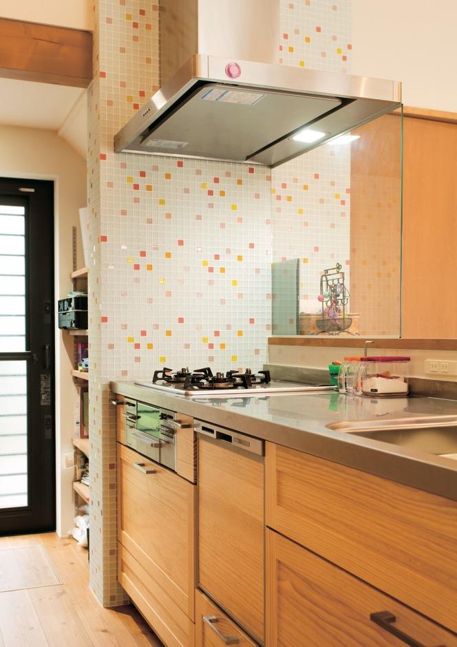 アトリエプラス【デザイン住宅、趣味、自然素材】側面の壁にモザイクタイルを貼った奥さま自慢のキッチン。奥にパントリーを設けている