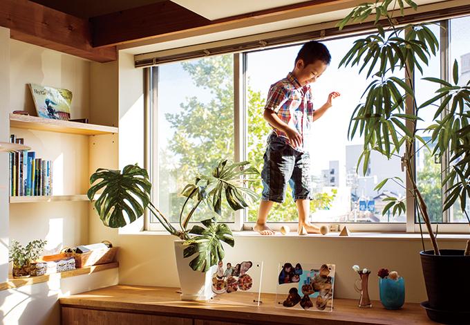アトリエプラス【デザイン住宅、狭小住宅、建築家】ダイニングの窓は子どもの身長ほどもある大きな樹脂サッシを採用。熟練職人の技が冴える木の造作棚も自慢