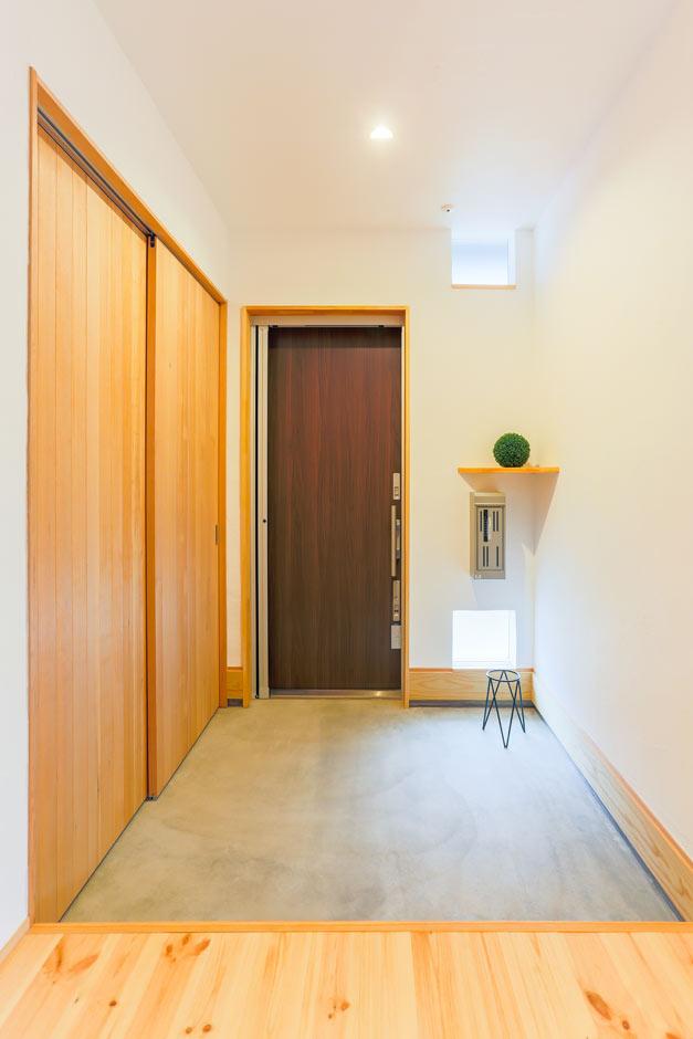 アトリエプラス【デザイン住宅、間取り、ガレージ】漆喰壁とモルタル仕上げが空間を引き締める。踏み込み汚れや少しのひび割れが良い味わいを出す