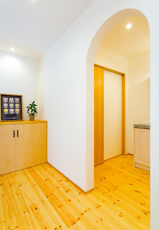 アトリエプラス【二世帯住宅、自然素材、インテリア】玄関から見えるRの開口が外観のカッコよさとのギャップを惹き立たせ、家全体をやわらかい印象に変える