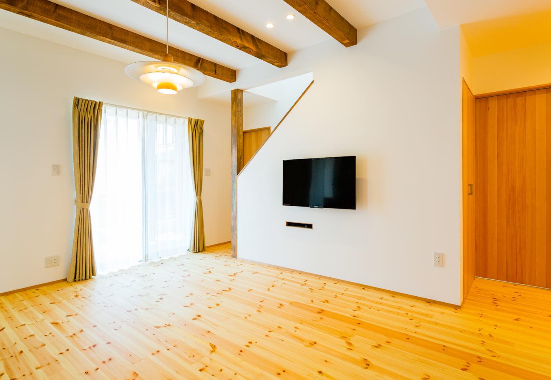 アトリエプラス【二世帯住宅、自然素材、インテリア】3本のウォールナット調の梁が空間を引き締める。テレビの配線はすべて階段下収納に隠してすっきり