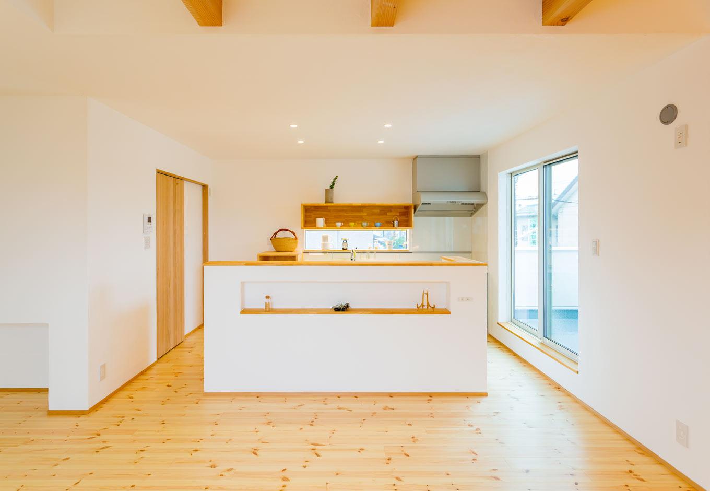 アトリエプラス【デザイン住宅、間取り、ガレージ】リビングからみたキッチンは、ニッチと造作の吊り棚のみが見える仕様に。手元が隠れるのは奥さまにはとって嬉しい工夫だ。漆喰の白と生活感を隠した空間で、シンプルおしゃれを演出