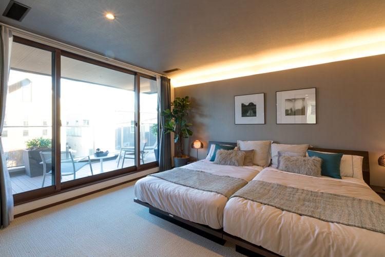 トヨタホームふじ【富士市今井348-4・モデルハウス】睡眠に配慮した優しい照明が室内をほんわりと照らす、大きな窓が印象的な主寝室。深い軒に守られたプライベートバルコニーが、ご夫婦のひと時を紡ぎ続ける