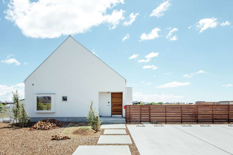 ワンズホーム【デザイン住宅、建築家、平屋】約45度の勾配屋根と、撥水性が高く自浄作用のあるドイツ製「Sto(シュトー)」の塗壁が潔く美しい。無垢アカシアのドアや、庭をドッグランのように囲む木塀とも相性がいい