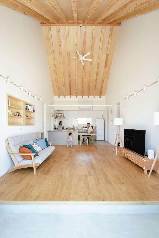 ワンズホーム【デザイン住宅、建築家、平屋】屋根勾配と登り梁を現した吹き抜けのあるLDKは広々。室内の床を覆う無垢の栗フローリングをベースに、白、グレーを組み合わせたコーディネートが清々しい。極限まで床をフラットに使える上吊り引き戸、床の継ぎ目素材まで選び抜く姿勢、植物を飾るために設置したキッチン照明レールなどに、夫婦の暮らしへの真摯な思いが垣間見える