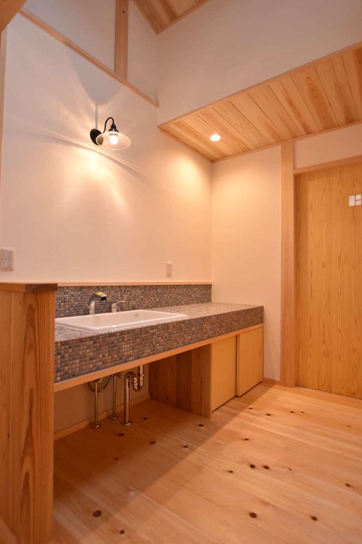 戸田工務店【和風、自然素材、平屋】浴室と分離し、廊下の一角に設けた洗面コーナー。カウンターはタイル張りにしてアクセントを付け、明るく清潔感にあふれた空間を演出