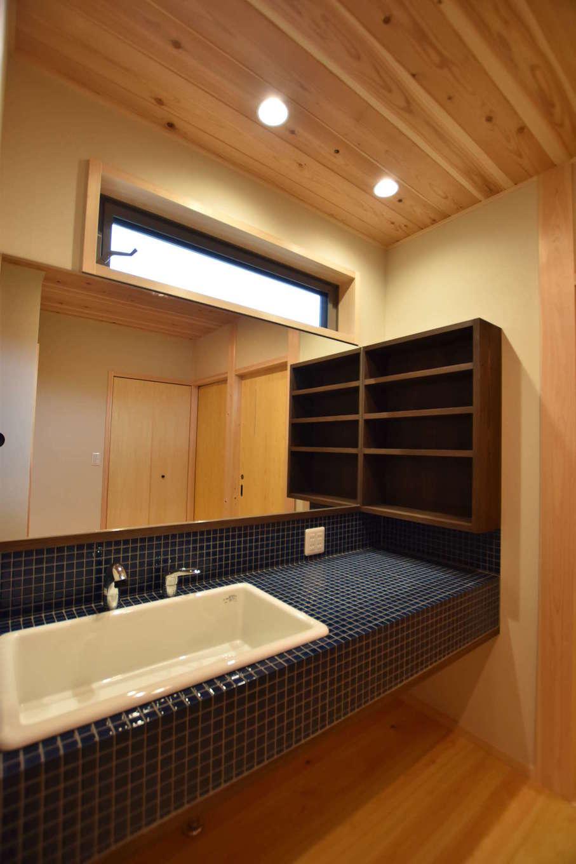 戸田工務店【和風、自然素材、間取り】洗面スペースは浴室と分離して廊下に配置。シンクとカウンター、鏡まで幅広く設け、使い勝手にゆとりを持たせた。ネイビーブルーのタイルがアクセントとなって木の空間を引き立てている
