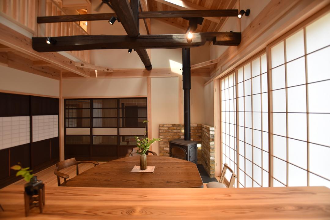 戸田工務店【和風、自然素材、間取り】L字型のキッチンから眺めたリビングダイニング。正面の古建具の先には「田」の字型の和室が広がる