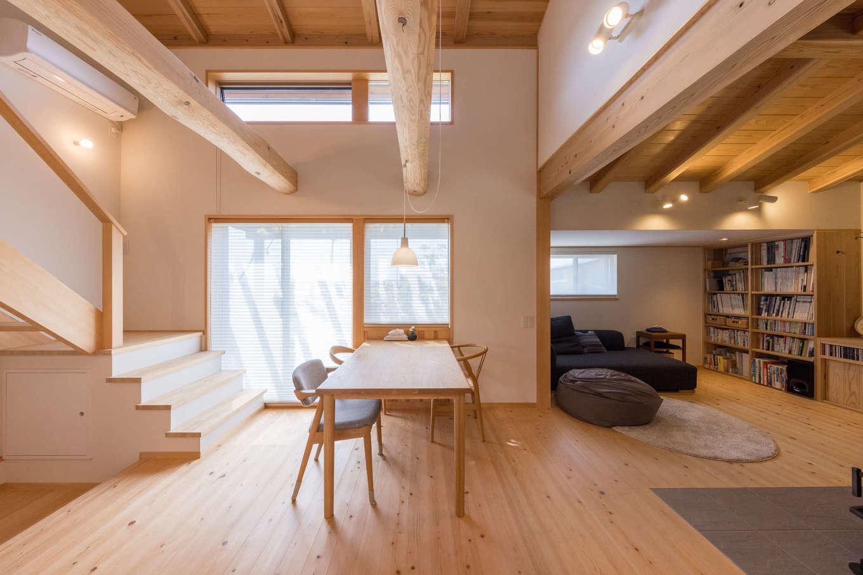 戸田工務店【デザイン住宅、自然素材、間取り】太い野物の梁が存在感を放つ、吹き抜けのダイニング。階段は幅を広めにしてあり、小さな子どもと一緒に上り下りしたり、大きな荷物を持ち運ぶのに便利。一方、リビングは天井高を抑えてダイニングとゾーン分けし、こもり感のあるくつろぎ空間が実現