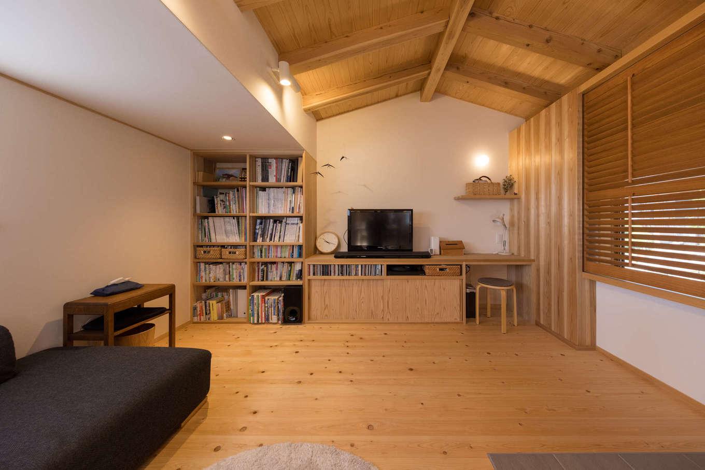 戸田工務店【デザイン住宅、自然素材、間取り】リビングはあえて天井を低くし、落ち着きのある空間に。無垢と珪藻土に包まれて、ゆったりリラックスできる。しまう物や使い勝手に合わせて造った造作家具を壁一面に設け、すっきりと片付いた空間をキープ。窓には木製のルーバーを設け、母屋からの目隠しに利用