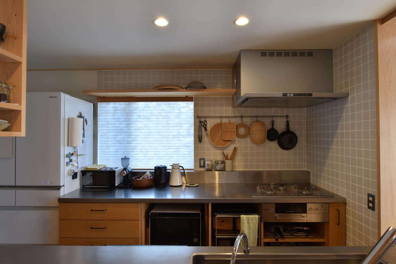 戸田工務店【デザイン住宅、自然素材、間取り】オリジナルの造作キッチンはステンレスカウンターと木目の扉を組み合わせたシンプルなデザイン。Ⅱ列型にして調理器とシンクを分けて配置し、奥さまの使い勝手に合わせて収納を設け、空間を無駄なく利用している