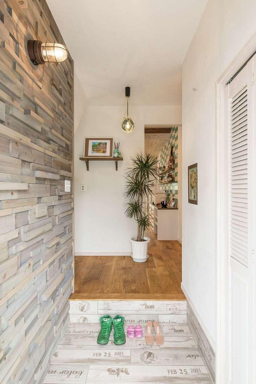 富士ホームズデザイン【デザイン住宅、輸入住宅、インテリア】凹凸感のあるウッドパネルと英字がプリントされたタイルでまとめた玄関。キーケースの扉には結婚式のブーケのドライフラワーが使われ、思い出も溶け込む