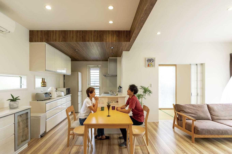 静鉄ホームズ【デザイン住宅、省エネ、間取り】家族の動線を熟慮したLDKは白を基調とした空間。キッチンの下げ天井と梁に施した木目調のクロスがアクセントに