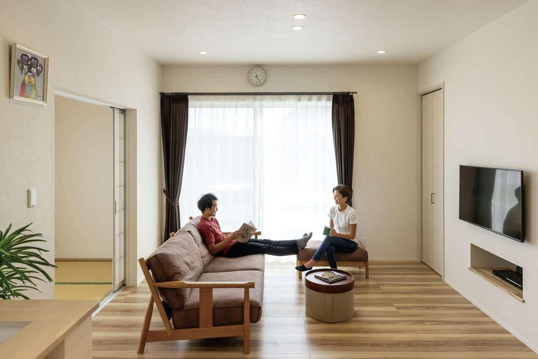 静鉄ホームズ【デザイン住宅、省エネ、間取り】天井を高くしたリビングは開放感たっぷり。冬は日中の日差しで夜まで暖かさをキープできる。テレビの下にはデッキを置くニッチを造作し、空間をすっきりと保つ
