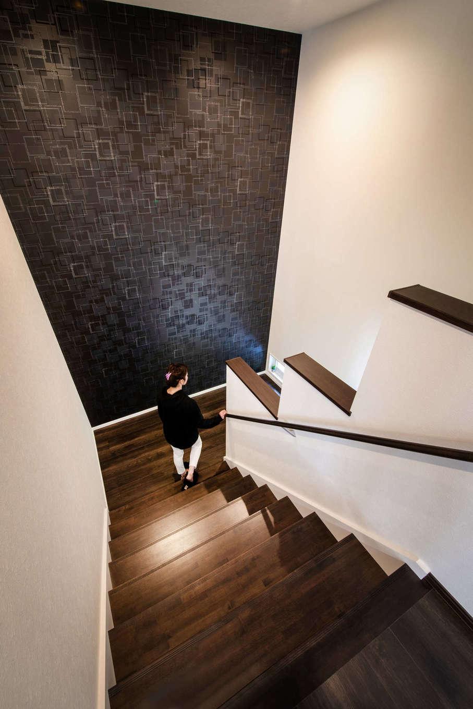 吉川住建【子育て、省エネ、ガレージ】幅1.5メートルの広い階段は、2人並んでも行き来が可能。天井まで至るアクセントクロスのスケール感に圧倒される