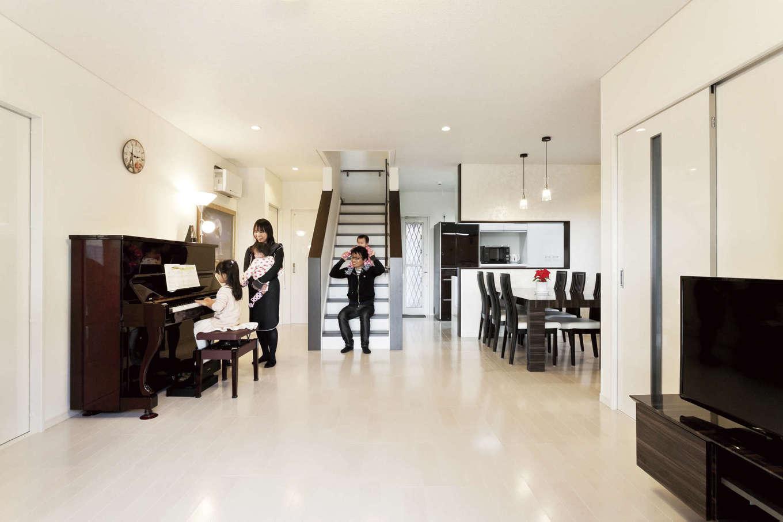 吉川住建【収納力、二世帯住宅、省エネ】中央にリビング階段を設けたLDKは約22.5畳の広々空間。テクノストラクチャー工法ならではの大空間を実現した。壁・床・天井とも白をベースに、ポイントに黒を配したシックなインテリア
