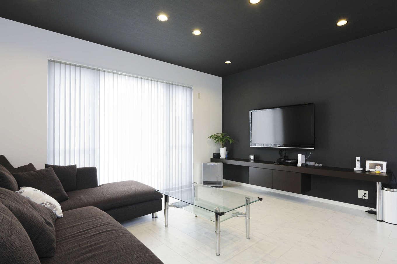 吉川住建【1000万円台、デザイン住宅、建築家】「バーのようなデザインに」と、リビングの天井や壁は黒を基調としたシックな雰囲気に。壁一面のテレビボードは造り付けで、おしゃれなデザインに仕上がっている。黒い天井に埋め込まれたダウンライトも、よりアーティスティックな雰囲気を演出している