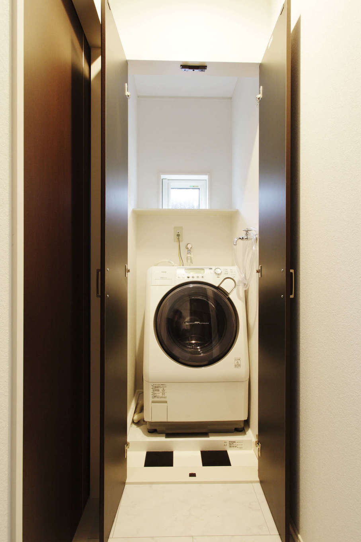 吉川住建【デザイン住宅、二世帯住宅、建築家】「生活感を出さず、常にすっきりした空間にしたい」とMさん。そのため、来客時に隠すことができるよう、洗濯機置き場にも扉を付けた。ここの床にも市松模様のデザインを採用