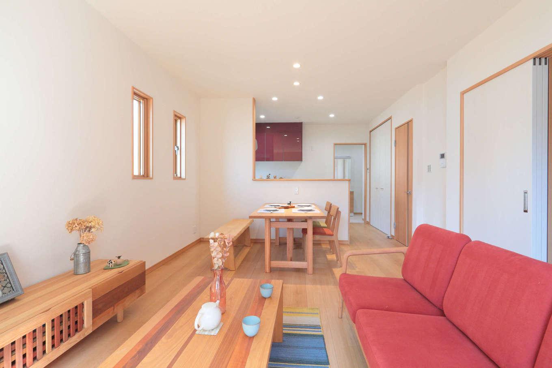 吉川住建【和風、二世帯住宅、自然素材】親世帯のLDKは16畳。赤いソファが挿し色に。テレビボードは造作