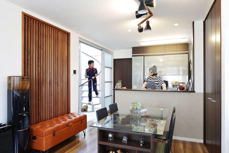 吉川住建【デザイン住宅、間取り、ペット】キッチンが中心の間取りで、リビング・ダイニング、和室、洗面脱衣室、2階へと昇るらせん階段がつながっているため、動線がよくて家事効率もUP。玄関ホールとLDKの間仕切りには木の格子壁を設け、格子をルーバーのようにずらすことで風が抜ける工夫も