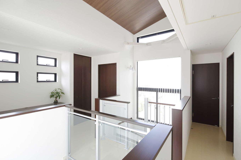 吉川住建【デザイン住宅、間取り、ペット】勾配天井で開放感あふれる2階ホール。キャットウォークのような渡り廊下の腰壁に透明パネルを使うことで、吹抜けの大きな窓から射し込む光を空間全体に行き渡らせ、より明るくなっている。奥には広いカウンターを造作したフリースペースもある