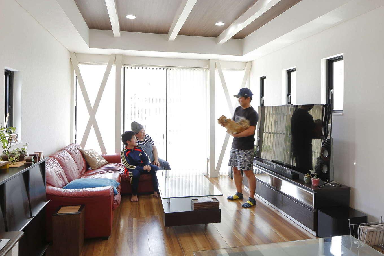 吉川住建【デザイン住宅、間取り、ペット】壁いっぱいの窓から光がたっぷりと射し込む明るいリビング。建物の耐震性を高める柱、クロスの筋交いをあえて見せるデザインや、折り上げ天井に木目調のクロスを採用し、インテリアのアクセントに