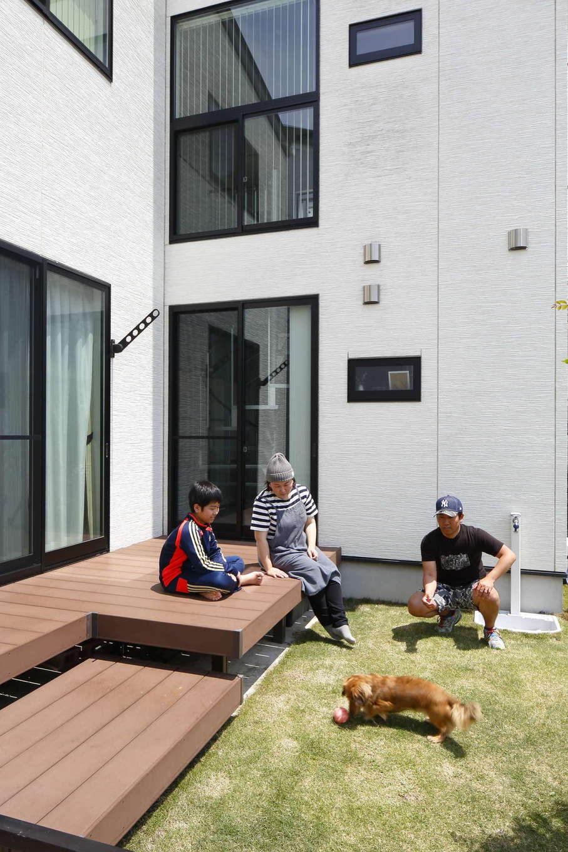 吉川住建【デザイン住宅、間取り、ペット】T字型の外観スタイルのちょうど角にある庭に、広いウッドデッキを設置。芝生でボール遊びをする愛犬と過ごす休日のひとときがうれしい。「ここで、バーベキューなどもよくやります!」