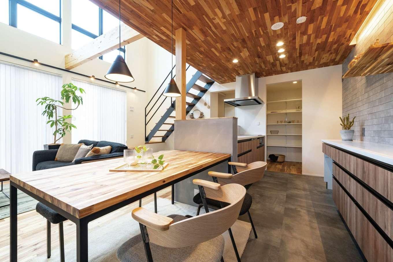 住家 ~JYU-KA~【デザイン住宅、ペット、建築家】キッチンの下がり天井は玄関ポーチと同じチーク材。バックカウンターのグレーの壁はイタリア製のタイル。吹抜けを通して2階の気配もわかるので安心