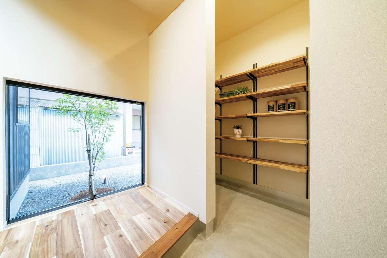 住家 ~JYU-KA~【デザイン住宅、ペット、建築家】玄関ホールの大きなピクチャーウインドウから見えるシンボルツリー。まるで額に飾られた絵画のよう