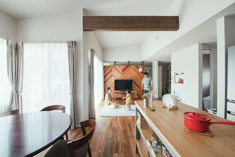 ワンズホーム【デザイン住宅、建築家、平屋】勾配天井に現しの梁が印象的なLDK。ダイニングからもリビングからも庭に出られる大窓があり、明るい光が注ぐ