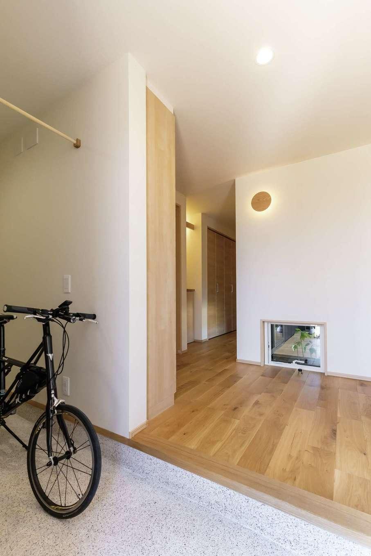 新栄住宅【趣味、自然素材、平屋】ロードバイクやベビーカーも収納できる土間仕上げの玄関。地窓に目線が抜けて中庭が見える