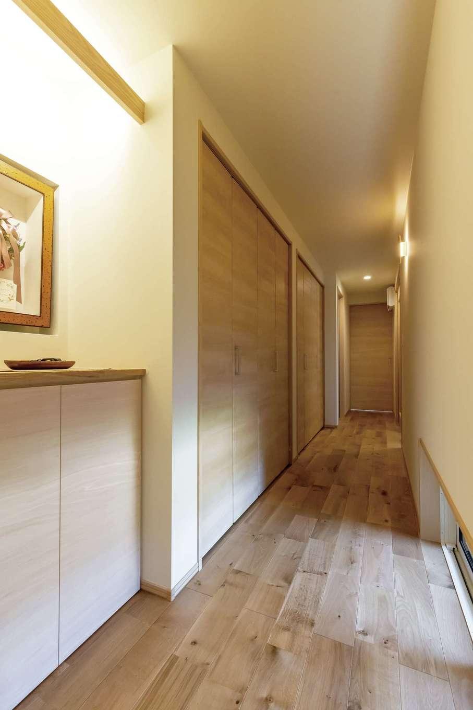 新栄住宅【趣味、自然素材、平屋】玄関から一直線に伸びていく長い廊下。大容量の壁面収納は造作