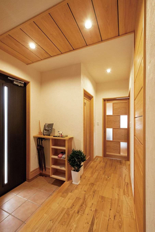 藤田工務店【二世帯住宅、自然素材、間取り】玄関ホールの天井から壁に続く木を使った意匠は、モデルハウスをお手本に。スリッパラックと傘掛け収納は造作で